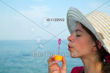 Teen Girl Blowing Bubbles At Sea Shore Stock Photo