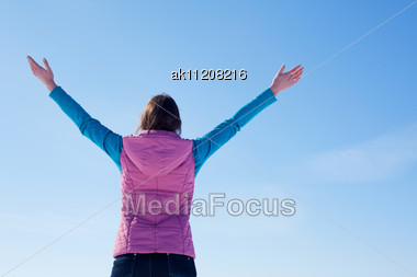 Teen Girl Staying With Raised Hands Against Blue Sky Stock Photo