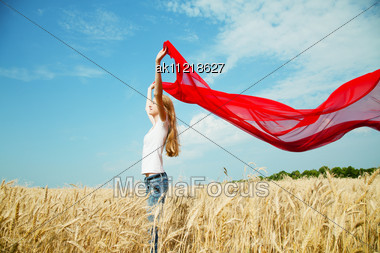 Teen Girl At A Wheat Field With Red Fabric Stock Photo