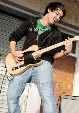 Teenage Boy Playing Electric Guitar Stock Photo