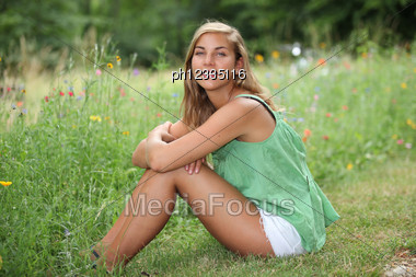 Teenage Girl Sitting In A Wild Flower Meadow Stock Photo