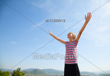 Teenage Girl Staying With Raised Hands Against Blue Sky Stock Photo