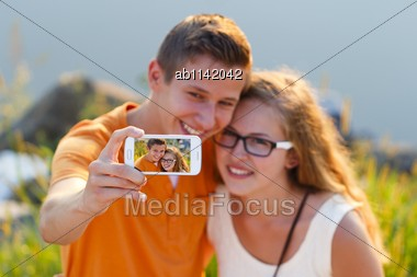 Teenage Lovers Taking A Selfie In The Sunset At Lakeside Stock Photo