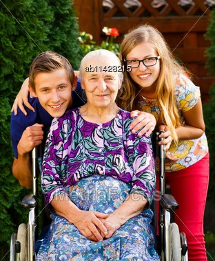 Teenager Grandchildren Visiting Their Old Disabled Grandmother Stock Photo
