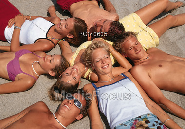 Teenagers Laying in Sand Stock Photo