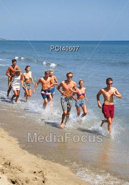 Teenagers Running Along Beach Stock Photo