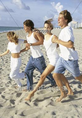 Teenagers Running to the Beach Stock Photo