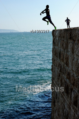 Teens, Jumping Into The Sea From A Height Of City Walls Of Acre. Stock Photo