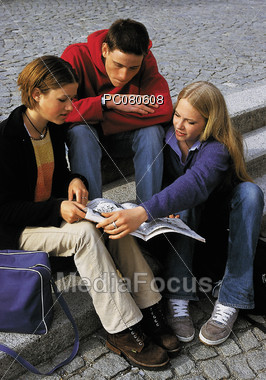 Teens Talking and Looking at Magazine Stock Photo