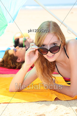 Teens Tanning On The Beach Stock Photo