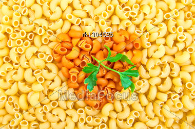 Texture Of The Yellow And Orange Pasta In The Shape Heart, A Green Sprig Of Parsley Stock Photo