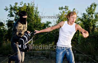 Thief In Mask Stealing A Backpack Stock Photo