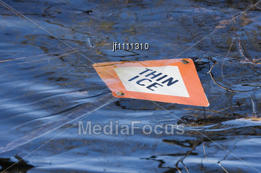Thin Ice Sign Floating In The Water Stock Photo