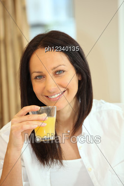 Thirty-ish Brunette Drinking Orange Juice Stock Photo