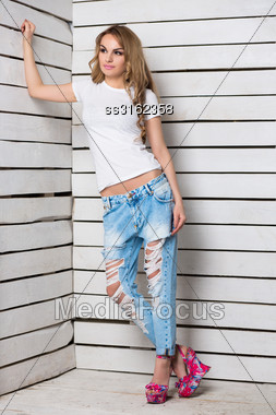 Thoughtful Blond Woman Posing In Blue Ripped Jeans And White T-shirt Near Wooden Wall Stock Photo