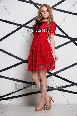Thoughtful Blond Woman Posing In Red Lace Dress Stock Photo