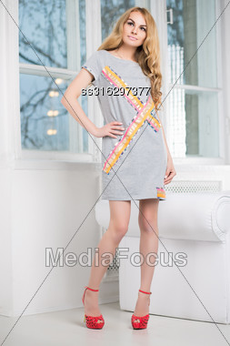 Thoughtful Blond Woman Posing In Short Gray Dress Near The Window Stock Photo