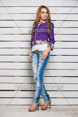 Thoughtful Blond Woman In Ripped Jeans And Purple Jacket Posing Near The White Wooden Wall Stock Photo