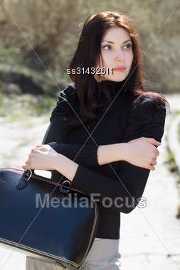 Thoughtful Brunette In Black Blouse With Big Bag Posing Outdoors Stock Photo