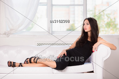 Thoughtful Brunette In Black Dress Posing On The White Sofa Stock Photo