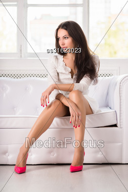 Thoughtful Brunette Wearing White Dress And Pink Shoes Posing On The Couch Stock Photo