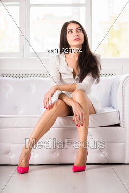 Thoughtful Pretty Brunette Posing On The Couch Stock Photo