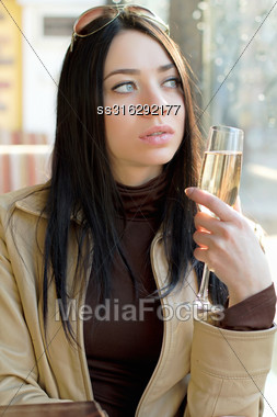 Thoughtful Pretty Woman Posing With A Glass Of Champagne. Isolated On White Stock Photo