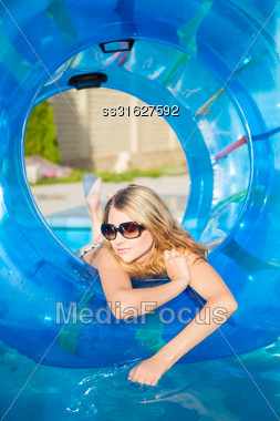 Thoughtful Young Blond Woman Posing With Rubber Ring In Swimming Pool Stock Photo