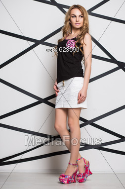 Thoughtful Young Blonde Posing In Black Top And White Skirt Stock Photo