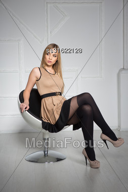 Thoughtful Young Blonde Posing In Sexy Beige Dress And Stockings Stock Photo