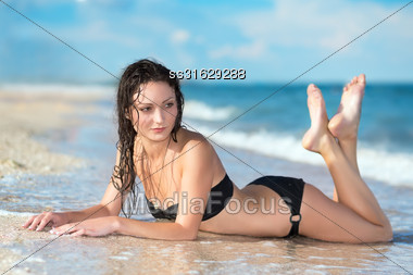Thoughtful Young Brunette In Swimsuit Posing On The Beach Stock Photo
