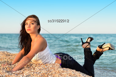 Thoughtful Young Brunette Wearing Jeans And Shoes Posing On The Beach Stock Photo
