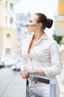 Thoughtful Young Brunette Wearing White Jacket Posing Outdoors Stock Photo