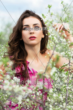 Thoughtful Young Curly Brunette Posing In Flowering Trees Stock Photo