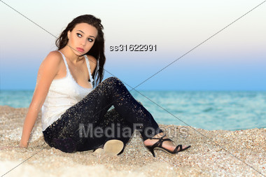 Thoughtful Young Lady Sitting On The Beach Stock Photo
