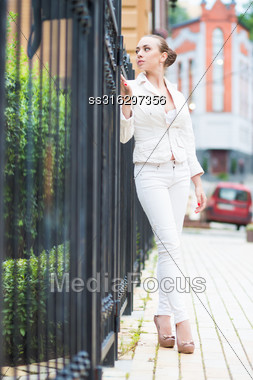 Thoughtful Young Woman Wearing White Pants And Jacket Posing Near Metal Fence Stock Photo