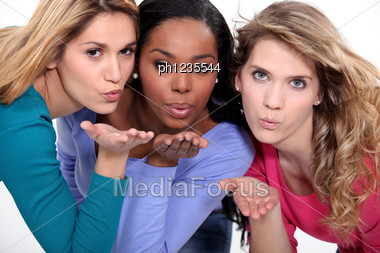 Three Attractive Women Blowing Kisses Stock Photo