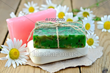 Three Bars Of Soap Pink, Green And White On A Piece Of Paper, Daisy Flowers On A Background Of Wooden Boards Stock Photo