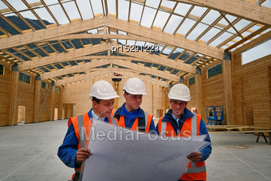 Three Builders Discuss The Plan For A Major Construction Job Stock Photo