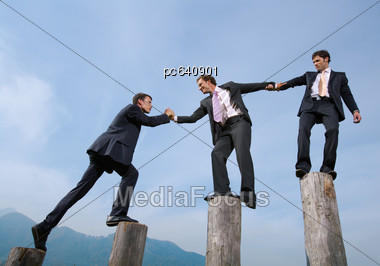 Three Business Men On Tree Trunks - Teamwork - Success Stock Photo