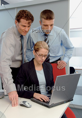 Three Business People Looking At Laptop Stock Photo