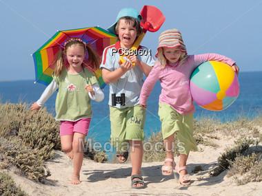 Three Children Walking through the Dunes Stock Photo