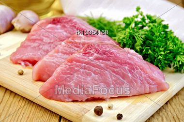 Three Chunk Of Pork, Garlic, Parsley, Dill, Knife, Pepper On A Wooden Boards Background Stock Photo