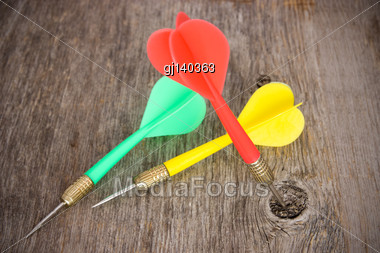 Three Color Darts On A Wooden Background Stock Photo