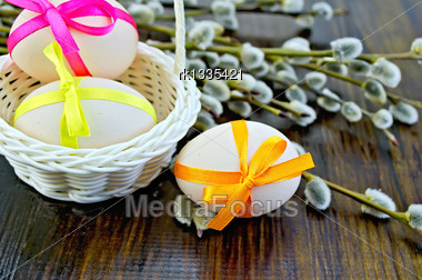 Three Easter Eggs Tied With Colored Ribbons, White Wicker Basket, Willow Twigs On A Wooden Board Stock Photo