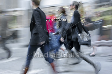 Three Female Tourists Walking On A Sidewalk, Intentional In Camera Motion Blur Stock Photo