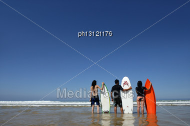 Three Friends Stood On Beach With Surfboards Stock Photo