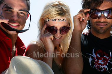 Three Friends Wearing Sunglasses Whilst Stood With Cabriolet Sports Car Stock Photo