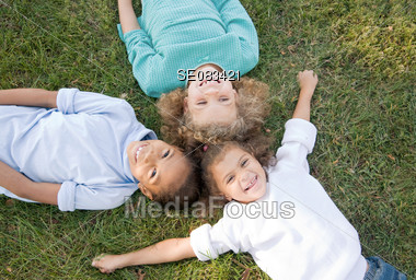 Three Girls Laying in the Grass Stock Photo