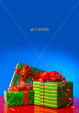 Three Green Presents Against Blue Background Stock Photo